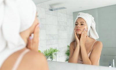 woman putting natural skincare products on her face