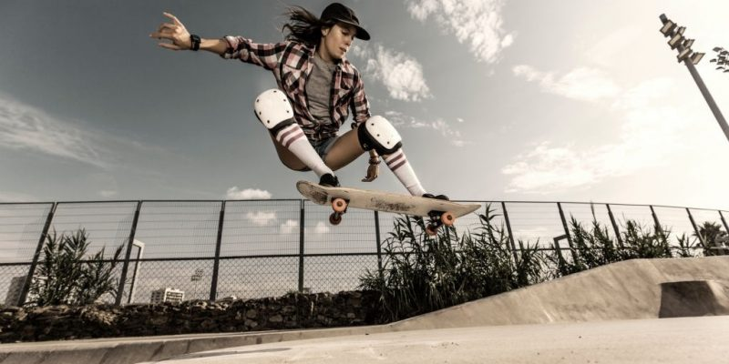 picture of a girl riding a skateboard with knee pads