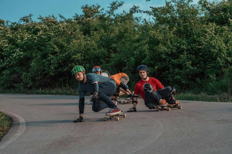 picture of boys riding a skateboards on a concrete whit full gear