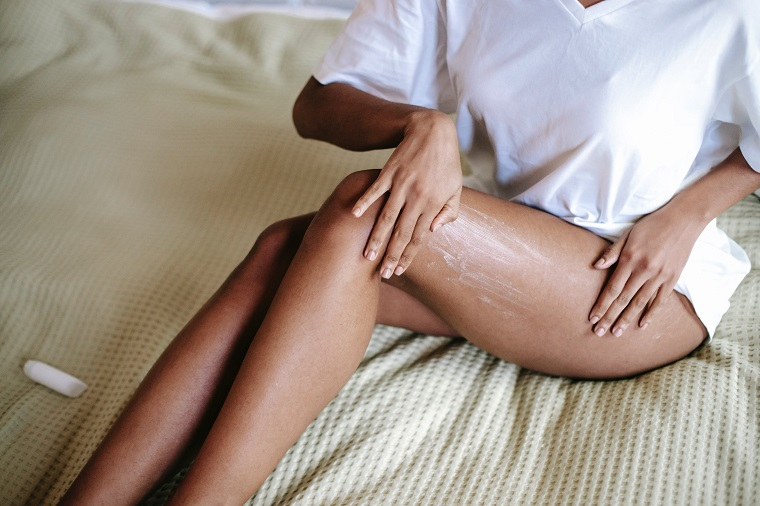 picture of person sitting in the bed in white shirt putting a cream on the legs