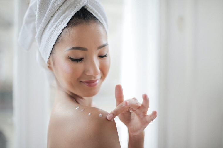 picture of a woman putting a moisturizer on her body