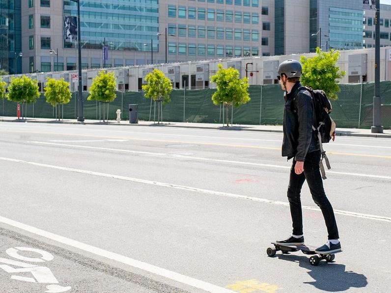 man riding an electric skateboard on the street