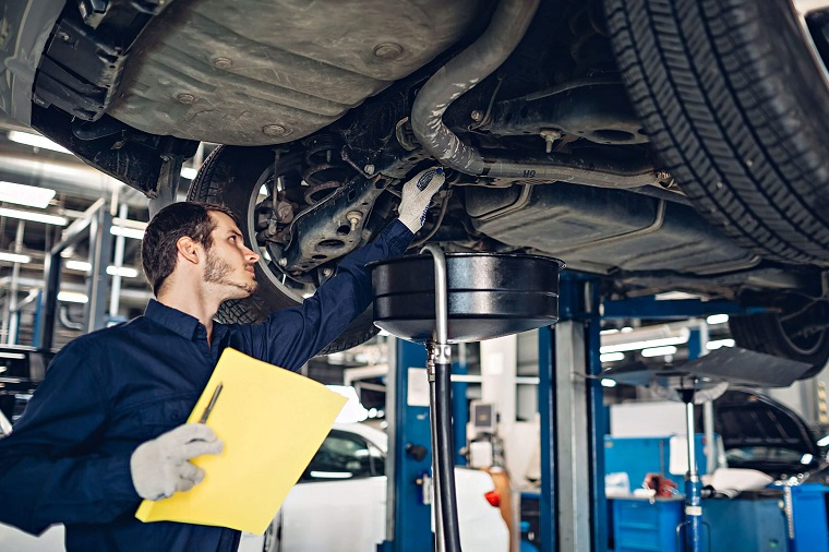 man looking at the bottom parts of a vehicle