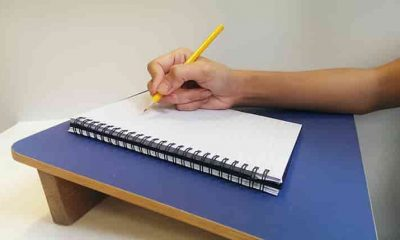 slant writing board with person's hand on it
